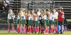 The varsity field hockey team meets on the sideline during a timeout. Photo by Travis Temple.