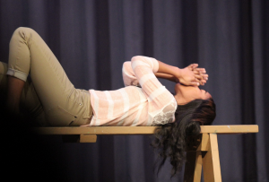 Senior Jamecia Woodson lies on a bench to start off the play with an impromptu warmup session. Photo by Ashli Moseley.