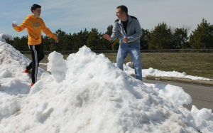 """Seniors Cooper Stegmann and Colton Smith play in the snow in the school parking lot. """"Because of the snow, we have to practice inside [for tennis] and we can't play on our courts. Our first game is in early March, so the snow has put us at a disadvantage for the early season,"""" Smith said. Photo by Debra Thomas."""